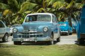 Vintage, retro classic cars parked in tropical garden near the beach and ocean — Stock Photo