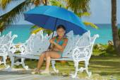 Happy little girl with umbrella, sitting on old style metal bench — Stock Photo