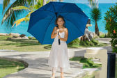 Little girl with blue umbrella enjoying her leisure time — Stock Photo