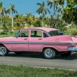 Pink classic vintage retro car parked on the road against gorgeous tropical garden — Stock Photo #53779225