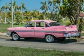 Růžový klasický vintage retro auto zaparkované na silnici proti nádherné tropické zahrady — Stock fotografie