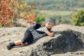 Happy, smiling little tired girl lying and resting on Niagara escarpment stone cliffs after hiking — Stock Photo
