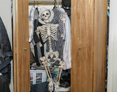 Skeleton sitting in the wardrobe-closet, wearing a white hat--  Everyone has a skeleton in their closets — Stock Photo
