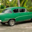View of old green, customized retro vintage classic car, parked against beautiful tropical garden background — Stock Photo #55735649