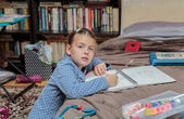 Beautiful fashionable little girl sitting in her room and doing home work — Stock Photo