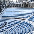View of outdoor amphitheater rows of  blue plastic seats covered in snow at winter time on sunny day — Стоковое фото #57625823