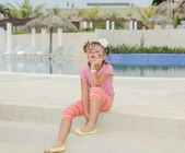 Unhappy little girl with painted face sitting on concrete steps near the swimming pool in background — Stock Photo