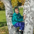 Smiling joyful little girl sitting between the birch trees in park — Stock Photo #59403865