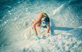 Bambina che gioca in sabbia sulla spiaggia vicino all'oceano — Foto Stock