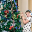 Charming fashionable happy girl decorating and preparing a Christmas tree in her room — Stock Photo #61737683