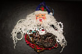 Decorative Santa Claus with various jewelry gifts under his beard — Stock Photo