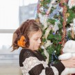 Pretty little girl holding and looking at plush angel bear toy beside Christmas tree — Stock Photo #64027323