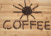 Written word and sun figure made of fresh coffee beans on old wooden background — Stock Photo