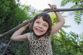 Joyful happy little girl with funny face playing in park — Stock Photo