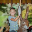 Funny joyful little girl riding on easter bunny carousel on sunny warm day — Stock Photo #68325671