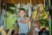 Funny joyful little girl riding on easter bunny carousel on sunny warm day — Stock Photo