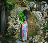 Little pretty styled girl standing near the cave in tropical garden — Stock Photo