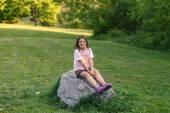 Kleines hübsch lächelnd glückliches mädchen sitzen auf einem großen stein im park bei sonne zeit einstellen — Stockfoto