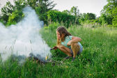 Child girl making fire in outdoor park — Stock Photo