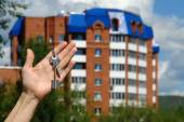 Man's hand with keys on background house — Stock Photo