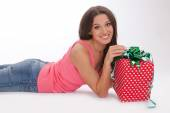 Beautiful woman in a red vest and blue jeans enjoys gift on Valentines day — Stock Photo