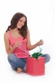 Beautiful woman in a red t-shirt and blue jeans enjoys gift on Valentines day — Стоковое фото