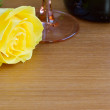 Yellow rose with a bottle of wine and a glass — Stock Photo #64321221