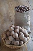 Hazelnuts in a cotton bag and walnuts in a wicker basket. — Foto de Stock