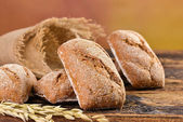 Wholemeal bread rolls on a wooden table — Stock Photo