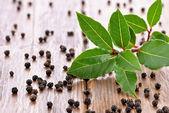 Fresh bay leaves and black peppercorns — Stock Photo
