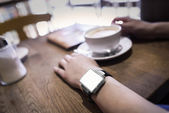 In coffee bar a woman using her smartwatch. — Stock Photo