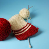 Red and white yarn balls with knitting needles on a blue background — Stock Photo