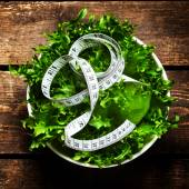 Fresh Salad with fitness measuring tape — Stock Photo