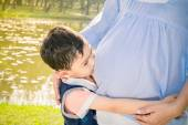 Asian boy kissing the belly of his pregnant mother — Stock Photo