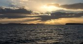 Sunset behind the clouds over sea — Stock Photo