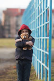 Portrait of a homeless boy with bear — Stock Photo