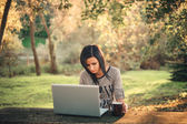 Girl and a laptop in the park — Stock fotografie