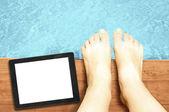 Kvinna ben med blank skärm tavlan pc vid pool — Stockfoto
