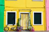 Colorful houses in Burano with a bike standing next to a flower  — Foto de Stock