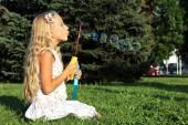 Girl in park blowing bubbles — Zdjęcie stockowe