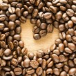 Heart shape made from coffee beans on wooden table. — Stock Photo #56102871