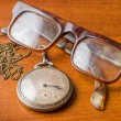 Old silver pocket watch and glasses — Stock Photo #64469345