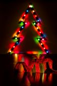 Christmas gift with blurred lights of tree — Stock Photo