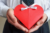 Man's hands with gift box in shape of heart — Stock Photo