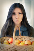 Surprised woman with a basket of ripe apples — Stock Photo