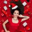 Funny Christmas Girl with Candy Cane surrounded by Presents — Stock Photo #58480331