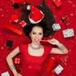 Funny Christmas Girl with Candy Cane surrounded by Presents — Stock Photo #58480341