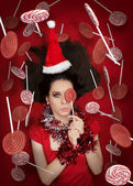 Funny Christmas Girl Holding a Candy Surrounded by Lollipops — Stock Photo
