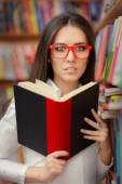 Young Woman with Glasses Reading Near Bookshelf — Stock Photo