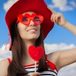 Beautiful Girl with Heart Sunglasses and, Lollipop and a Straw Hat on Blue Sky — Stock Photo #62733055